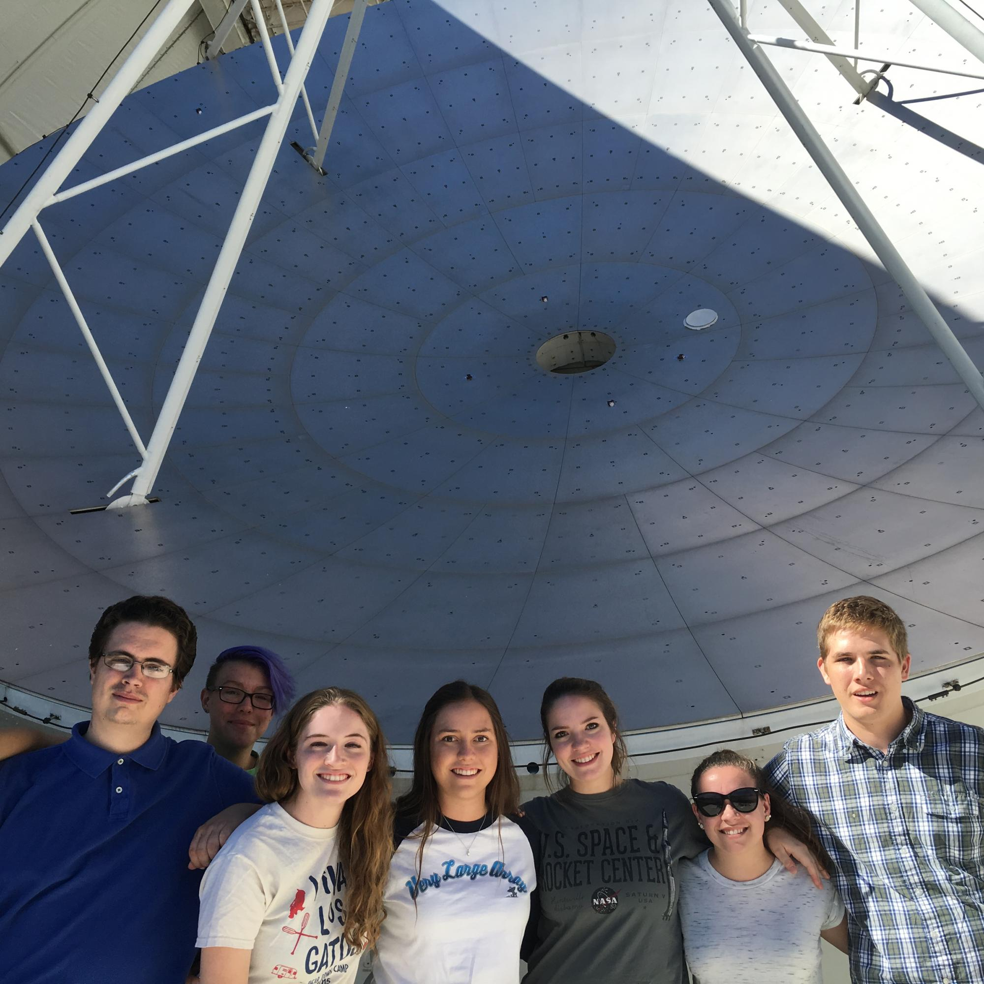 Calahan  and other UA undergraduate students pose in front of the dish of 12-meter radio telescope on Kitt Peak.