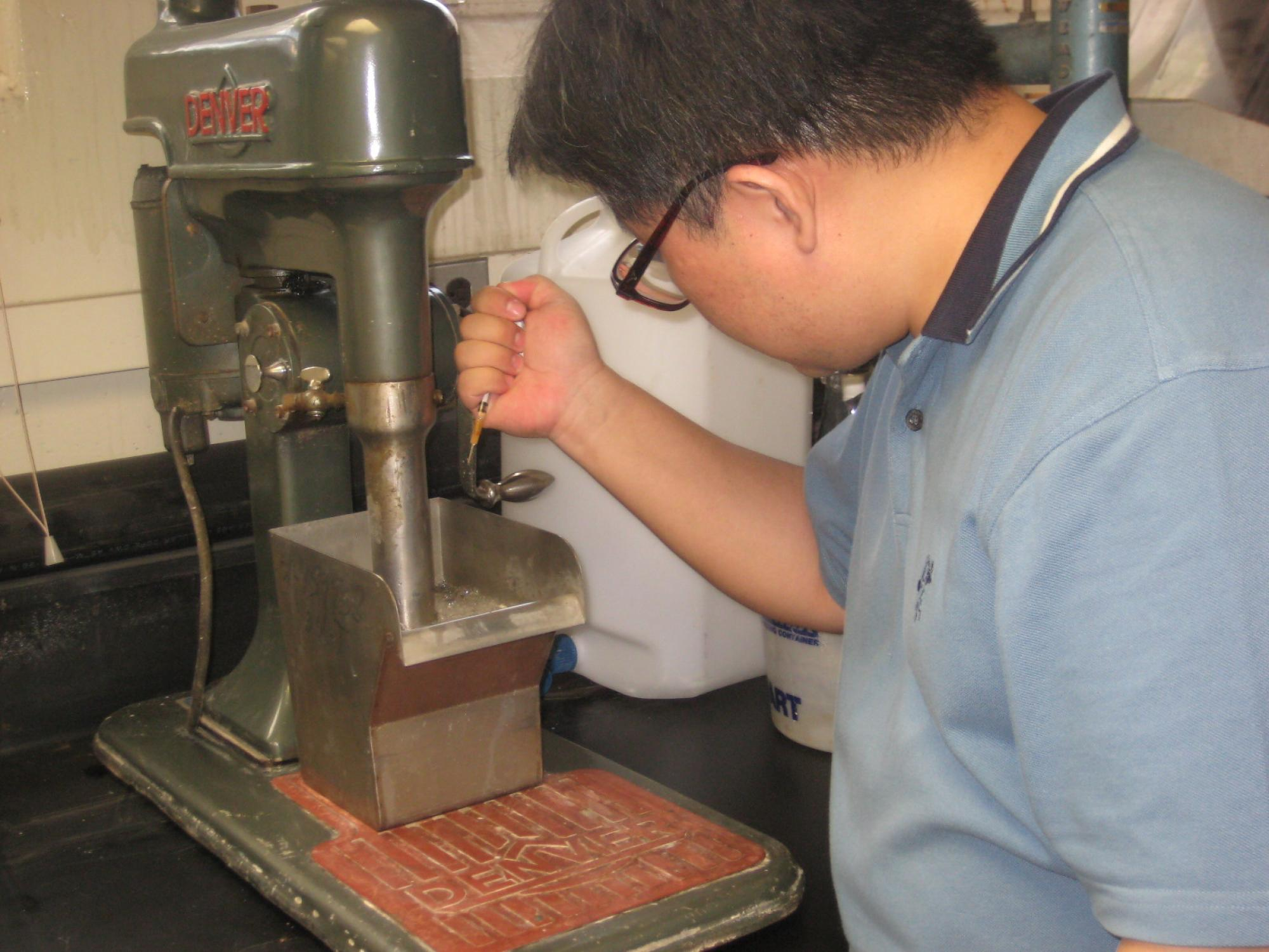 Jinhong Zhang, assistant professor of mining and geological engineering, injects just a few drops of chemical into a copper collection tank to create a layer of fine bubbles. The process brings copper particles to the surface for collection.