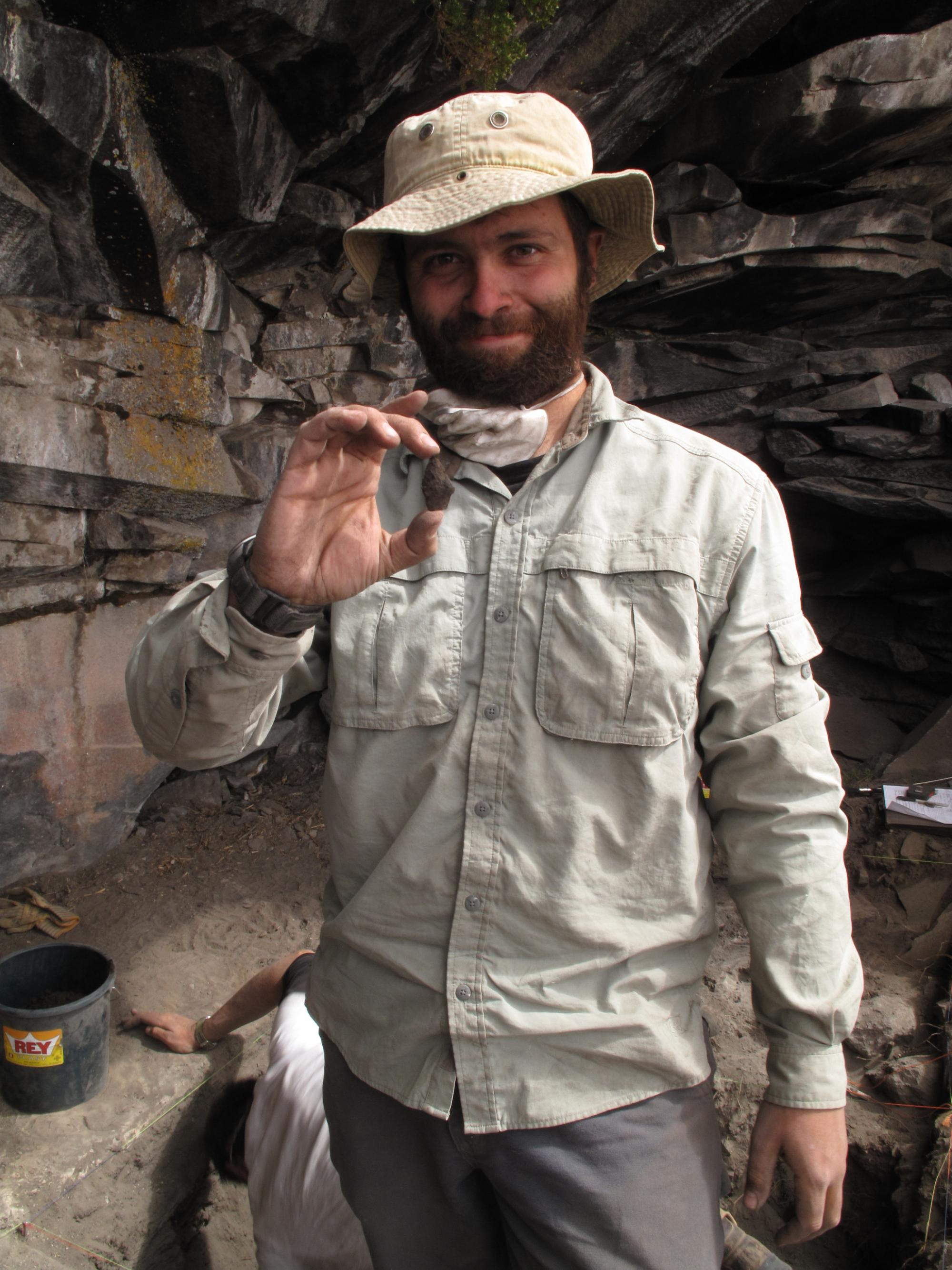 David Reid, a member of the archaeology team, holds up a projectile point fragment left behind by the first known high-altitude settlers.