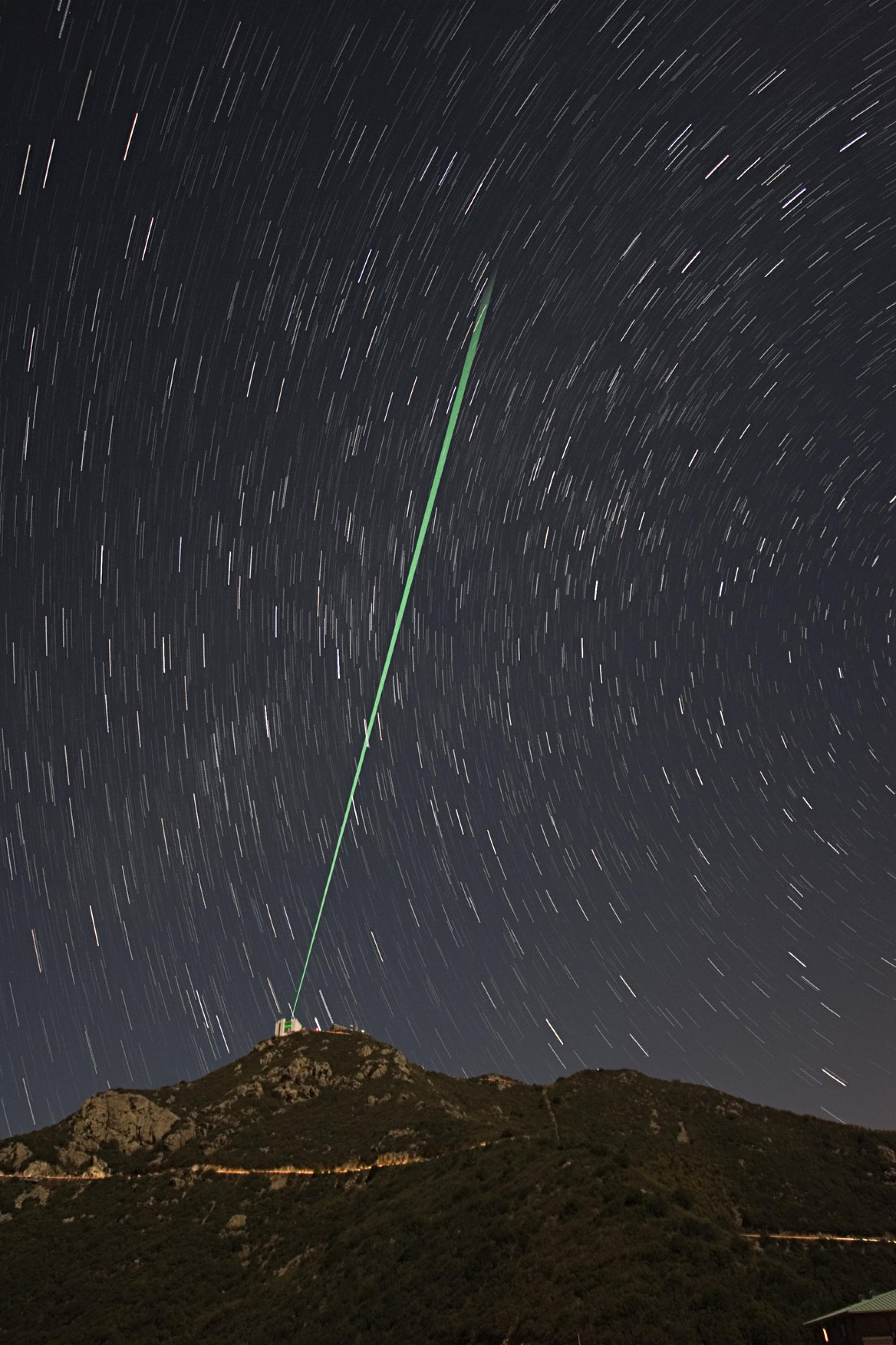 A bundle of laser beams creates five artificial stars in the night sky above Mount Hopkins in Southern Arizona. Laser light reflected by air molecules is analyzed by a computer that drives the actuators on the adaptive mirror.
