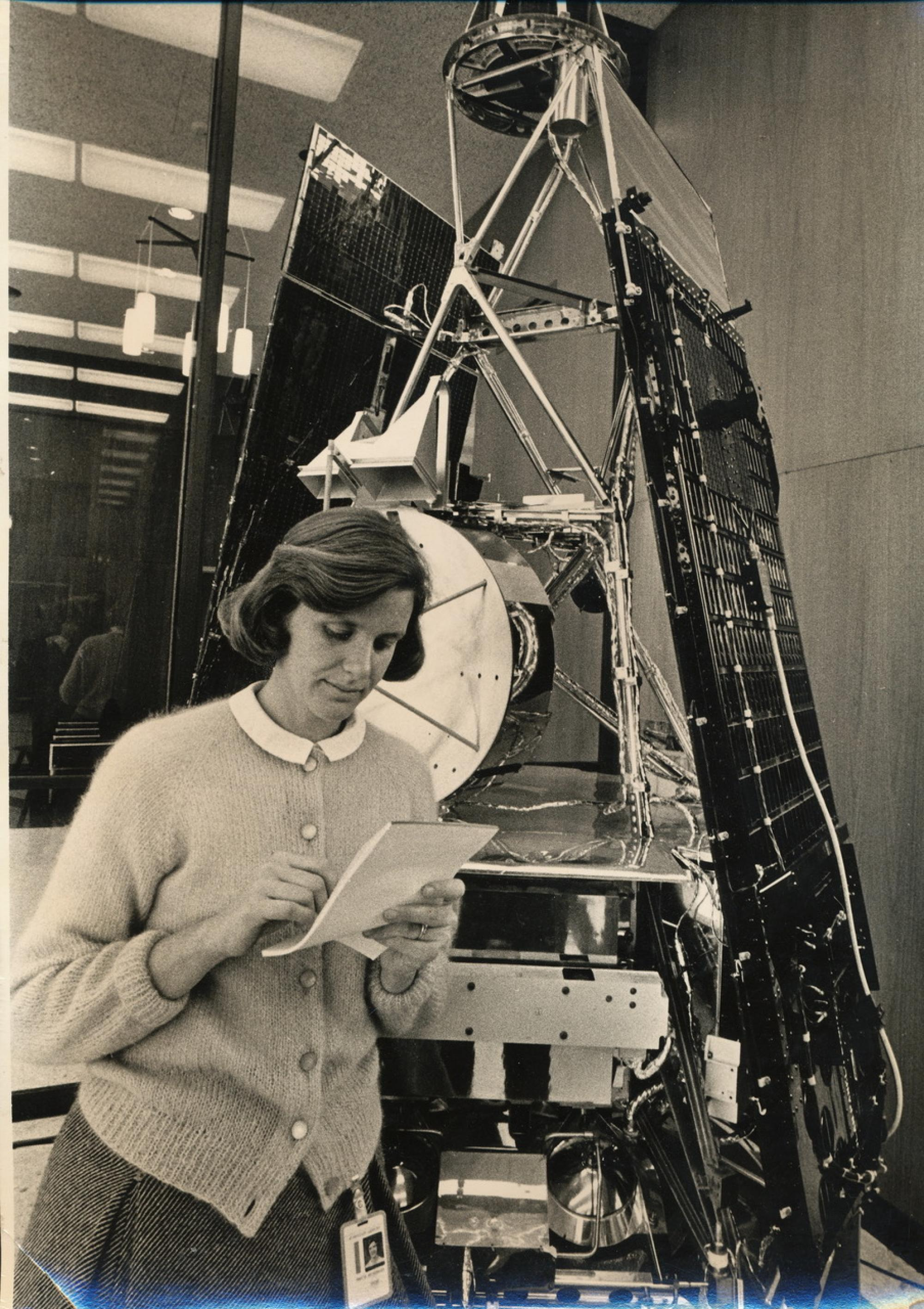 Marcia Neugebauer  with a model of Mariner 2, the first spacecraft to successfully fly by a planet. Neugebauer was part of a team that had designed an instrument aboard Mariner 2 that confirmed the solar wind as a constant stream of particles.