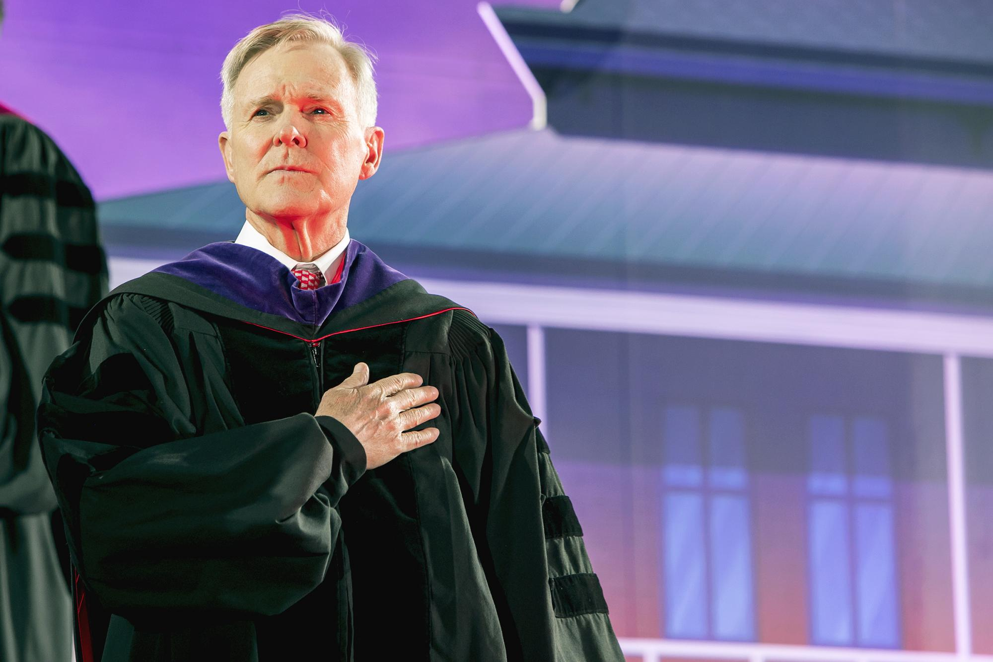 Commencement keynote speaker Ray Mabus stands at attention during the singing of the national anthem.