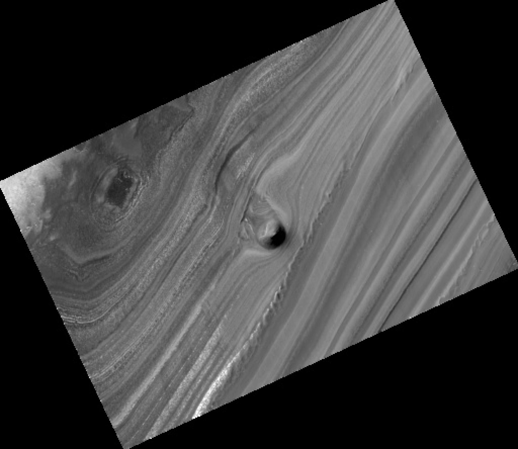 The UA's HiRISE camera on NASA's Mars Reconnaissance Orbiter found this odd, solitary hill part-way down an exposed section of Mars' north polar layered deposits. The 40-meter  high conical mound is likely the remnant of a buried impact crater, UA planeta