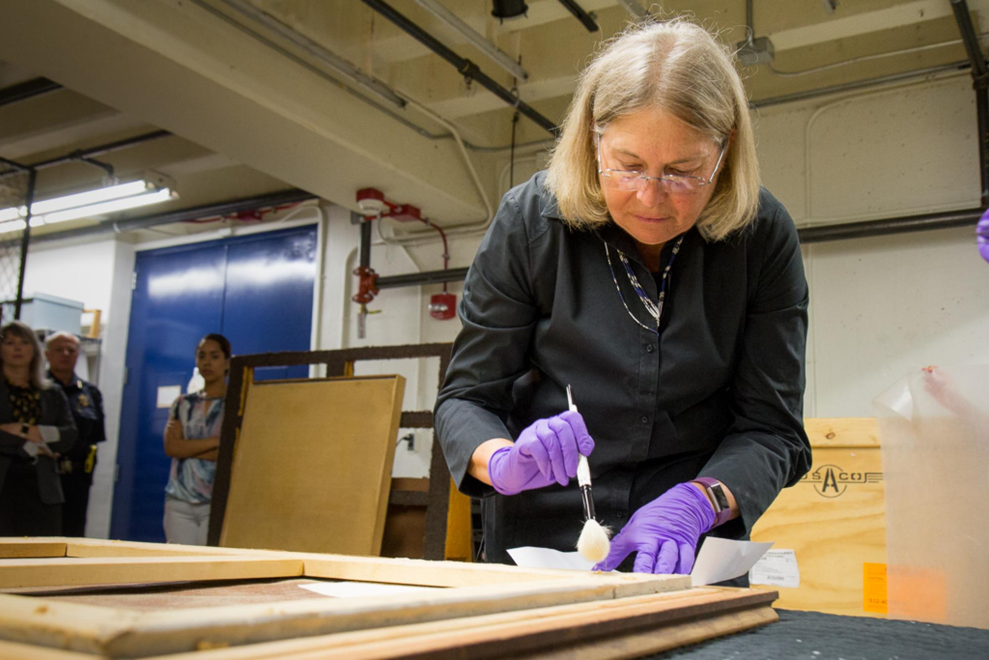 "Nancy Odegaard uses a brush to remove dust from ""Woman-Ochre."" Odegaard is a world-renowned conservator who works at the Arizona State Museum on the UA campus."