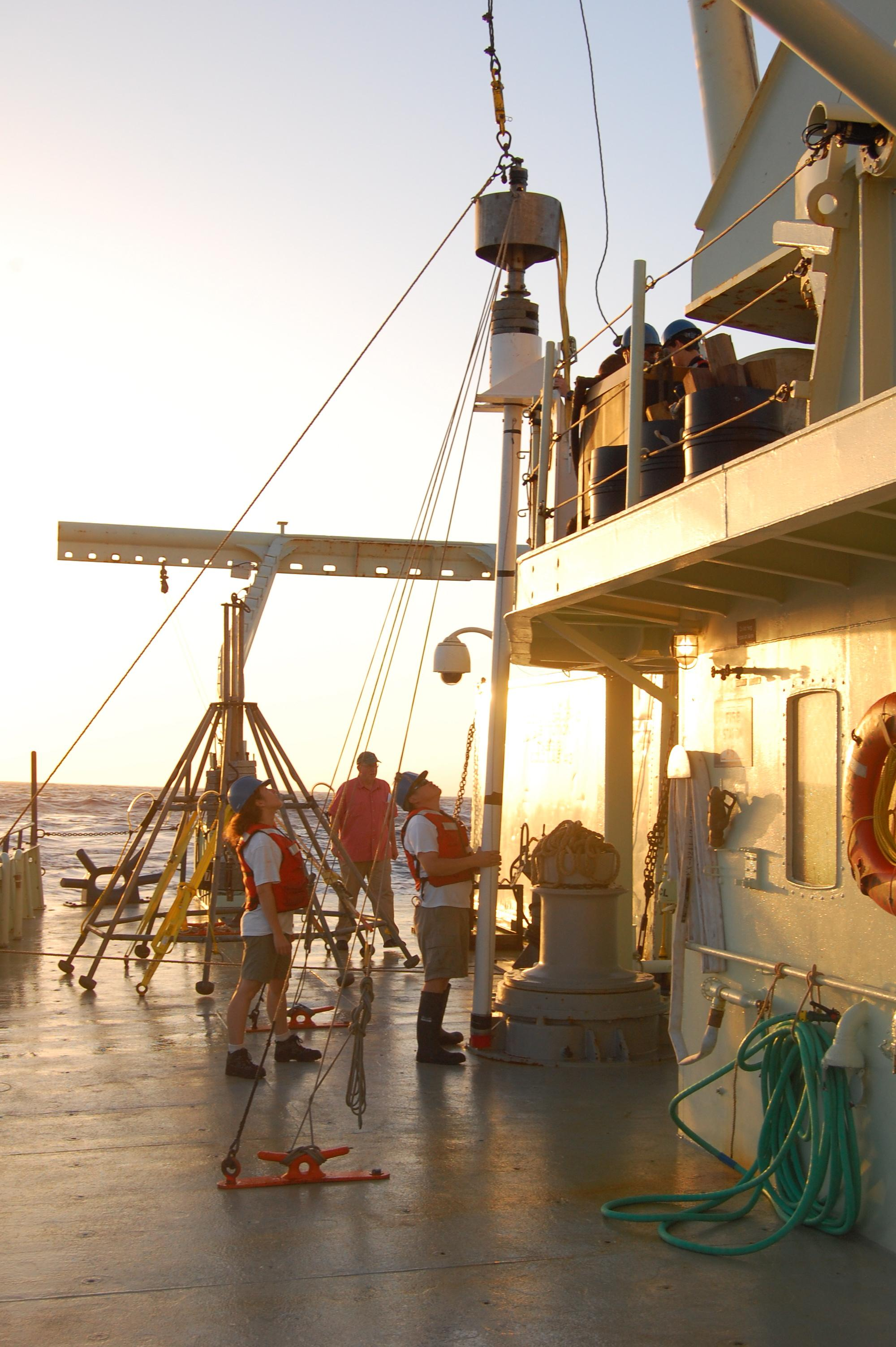 A researcher stares up at the 20-foot-long coring device that will be lowered over the side of the R/V Oceanus. The resulting core of marine sediments from off the West African coast will contain sediments laid down over about 40,000 years.
