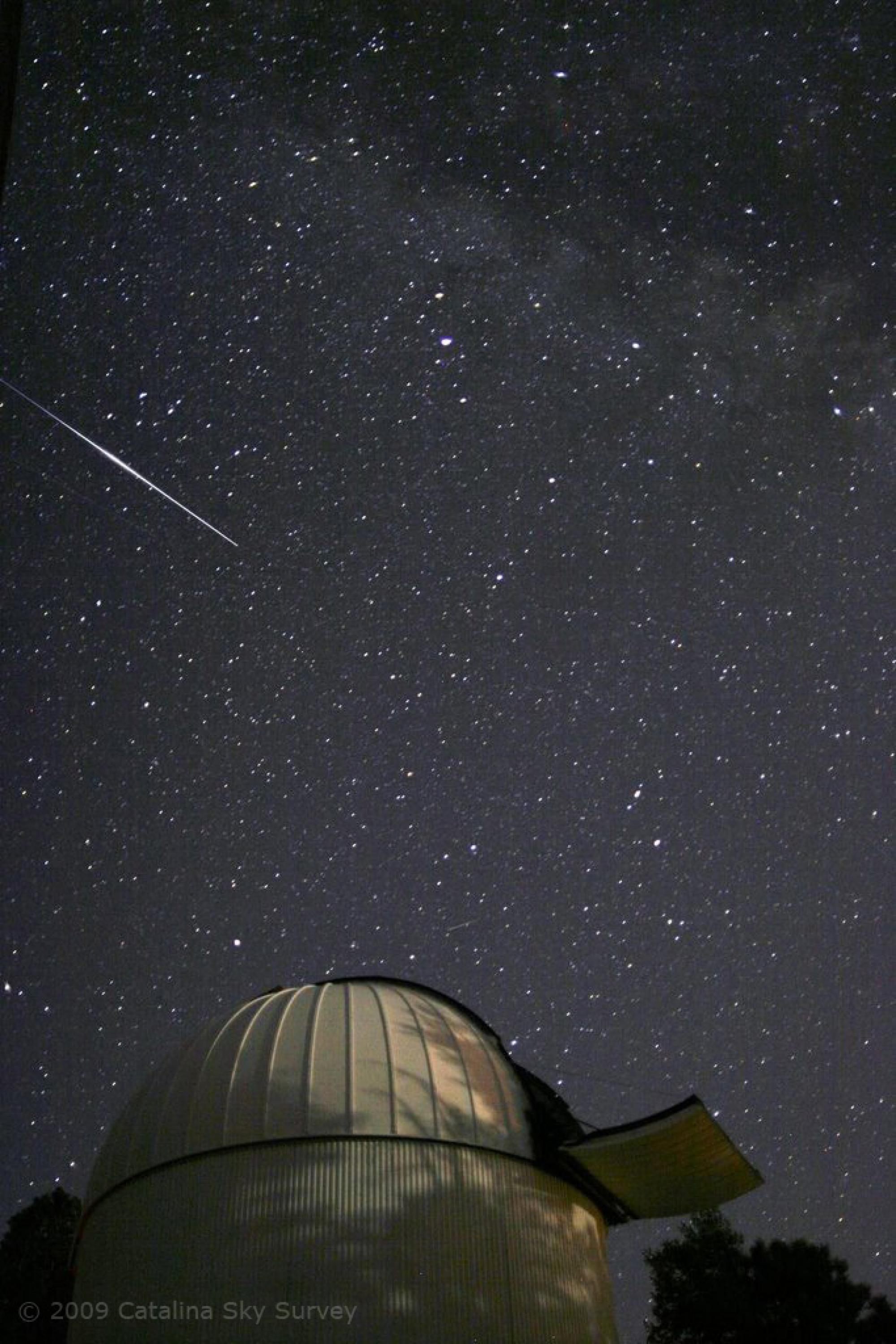 A meteor streaks through a starry sky above the Catalina Sky Survey Schmidt Telescope located on Mt. Bigelow in the Catalina Mountains just north of Tucson, Ariz.