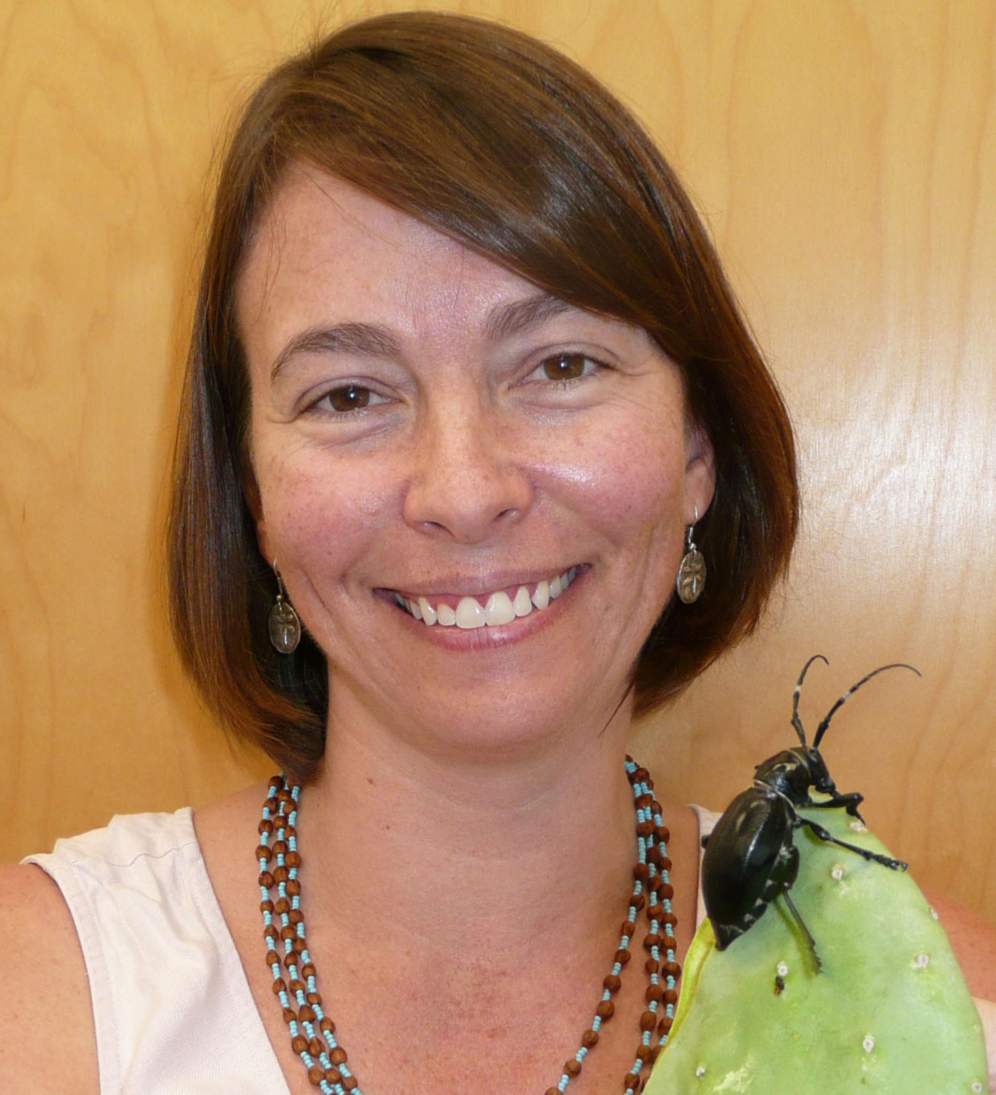 Wendy Moore with a Cactus Longhorn Beetle. This species has fused wing covers, preventing the beetle from flying but helping it retain precious moisture.