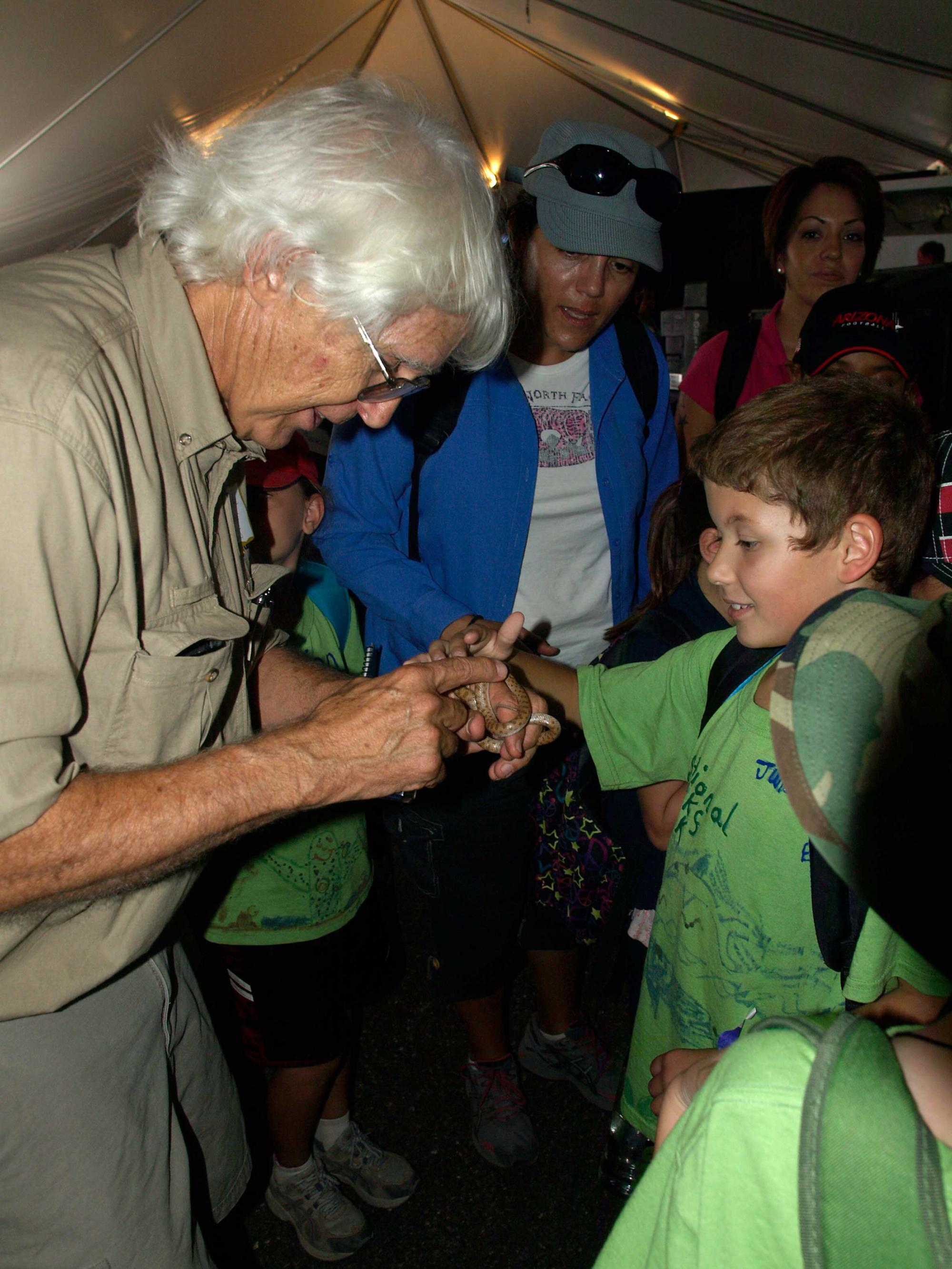 A school boy pets a night snake presented by UA reptile expert Cecil Schwalbe.