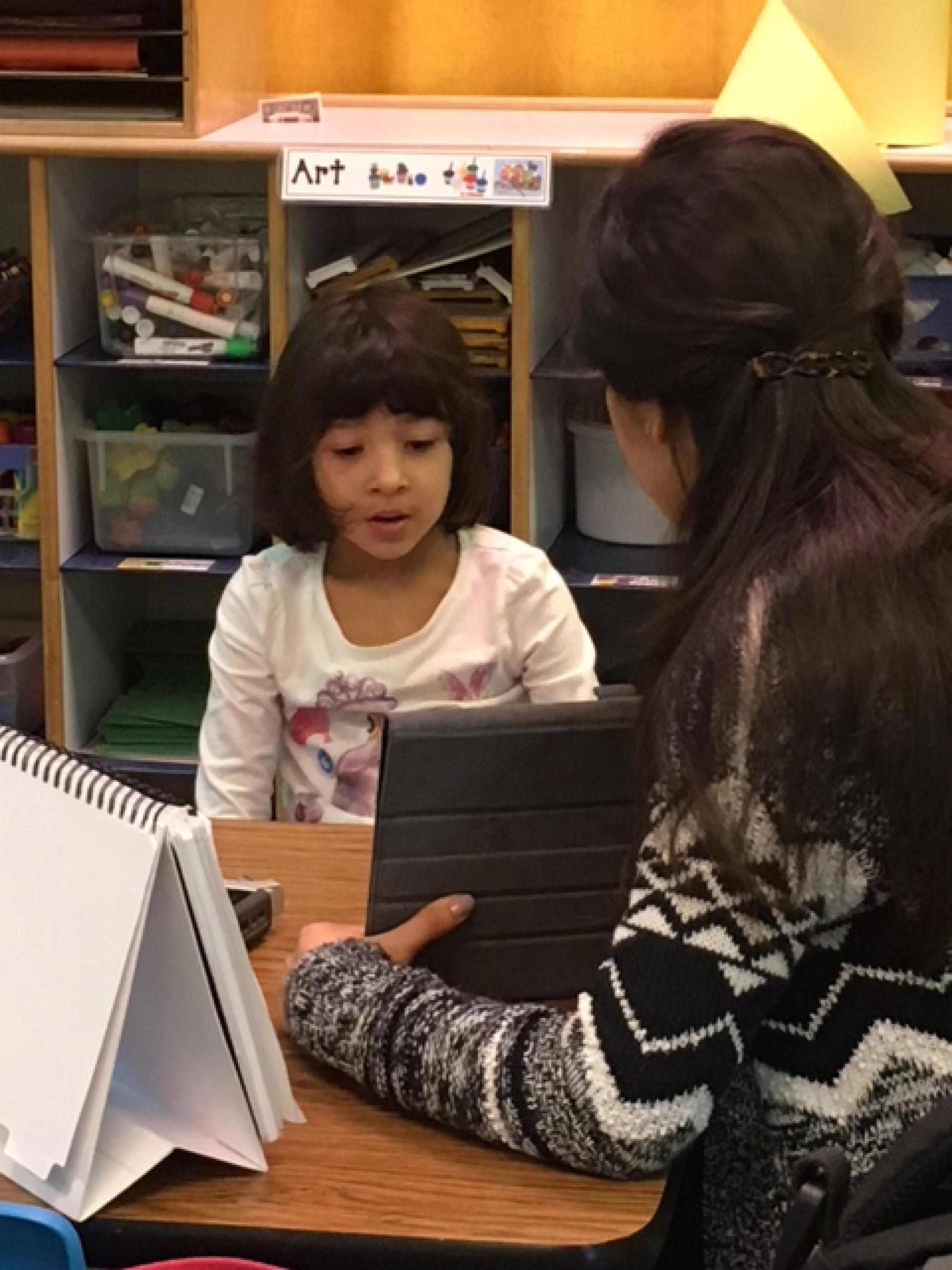 Pantoja asks a bilingual young girl to identify pictures on a tablet. Her answers are recorded and analyzed to determine if she is having trouble with speech sound production.