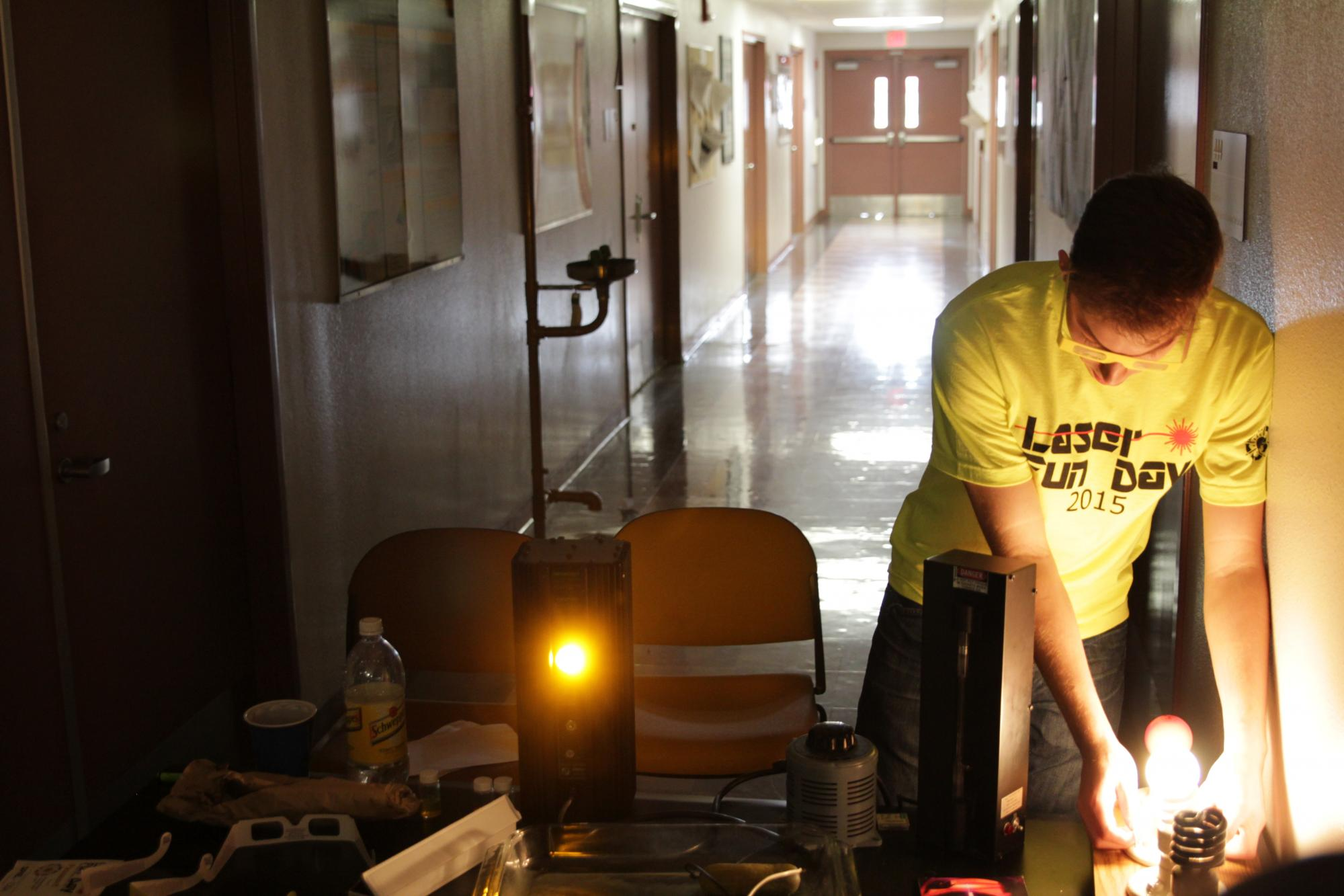 A student volunteer sets up an experiment for Laser Fun Day.