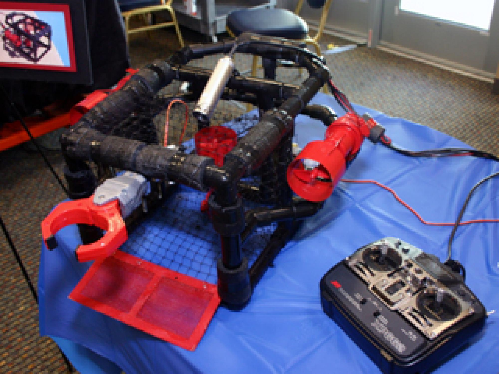 The robot submarine has two side-mounted motors that make it go forward and reverse. The motors run in opposite directions to make it turn. Since the sub was built to have neutral buoyancy, the vertical motor controls its depth. The robotic arm is used fo