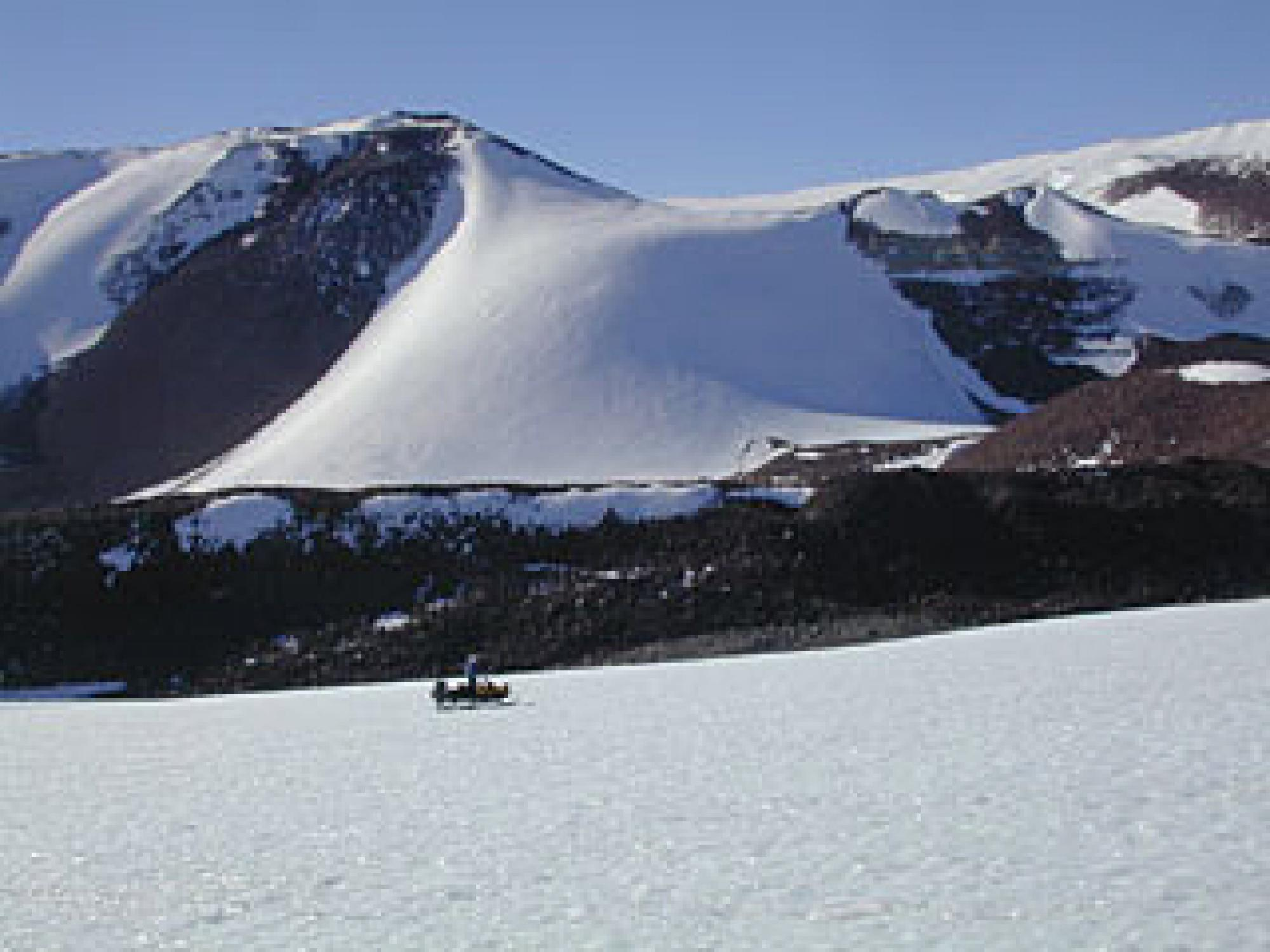 Cruising the base of an Antarctic mountain range, searching for meteorites, on an austral summer day.