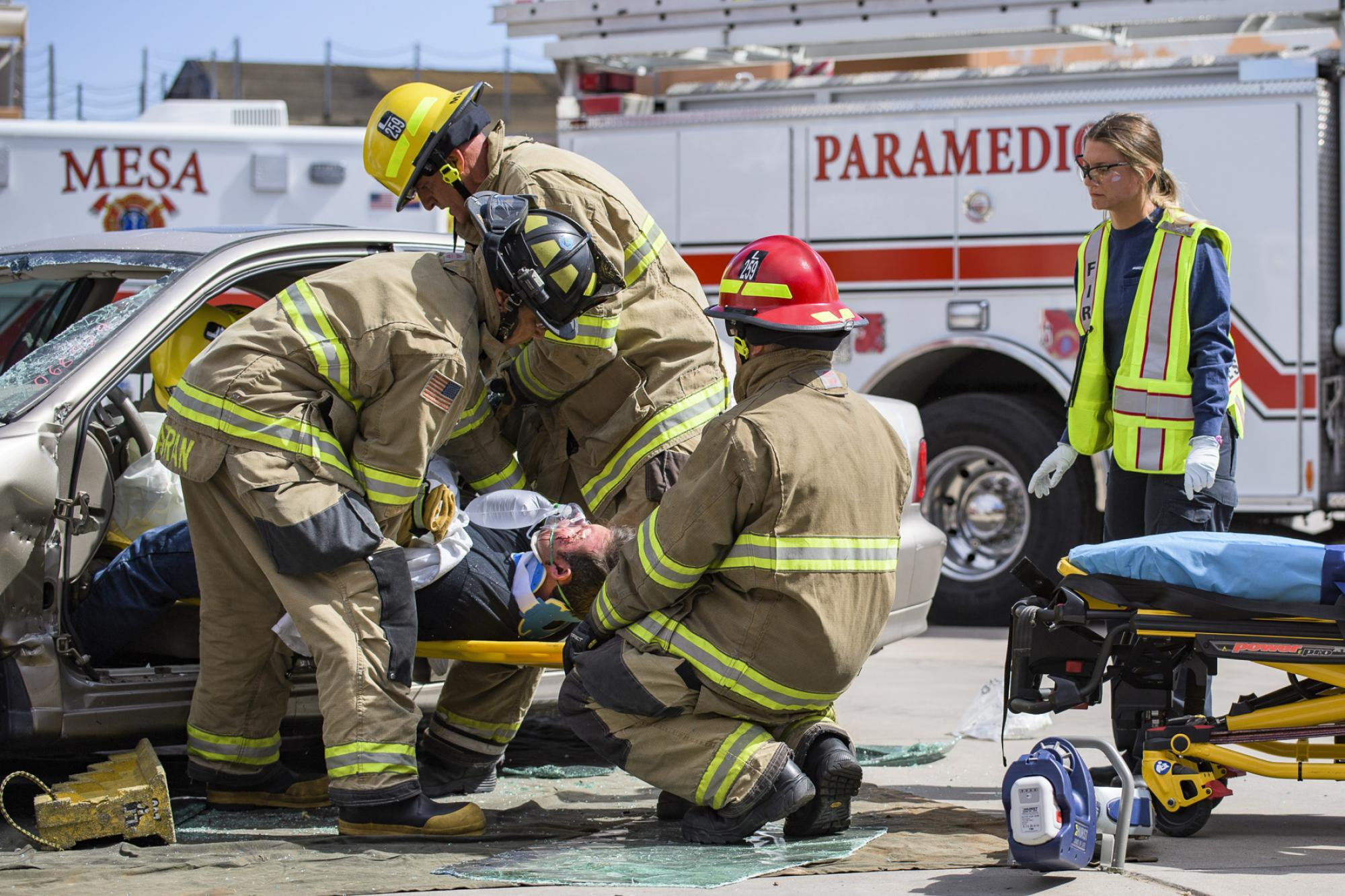Firefighter and paramedic personnel extricate a crash victim during a simulated auto accident.