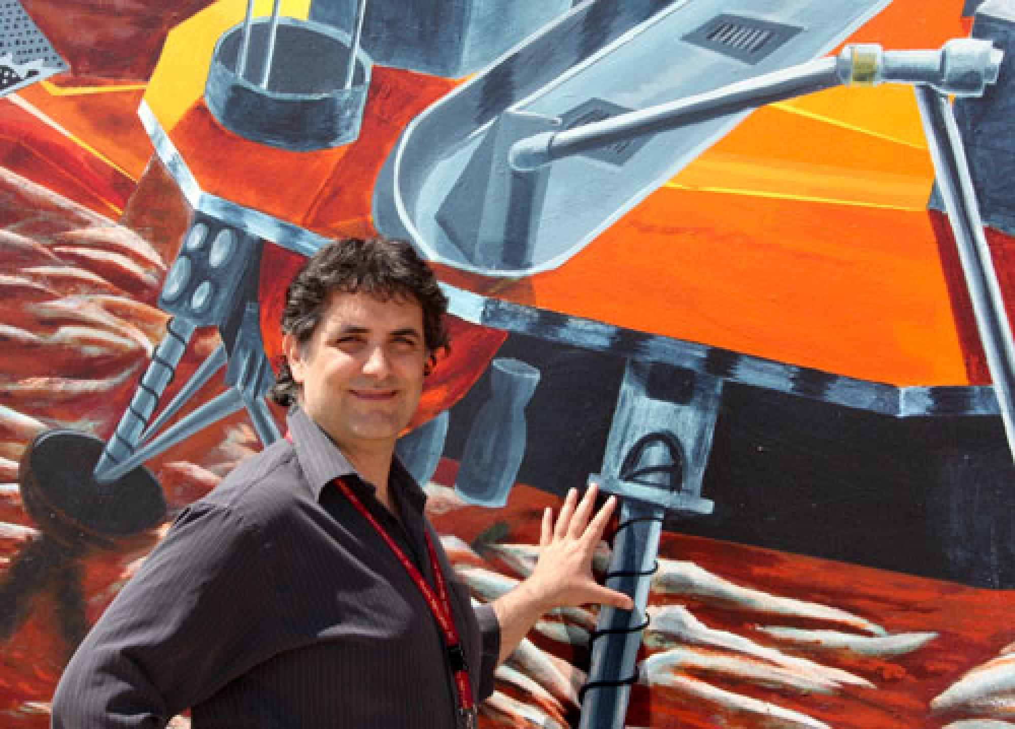 Assistant Professor Roberto Furfaro stands by the mural on the wall of LPL's OSIRIS-REx Science and Processing Operations Center in Tucson, Ariz., which is home to his Space Systems Engineering Laboratory.