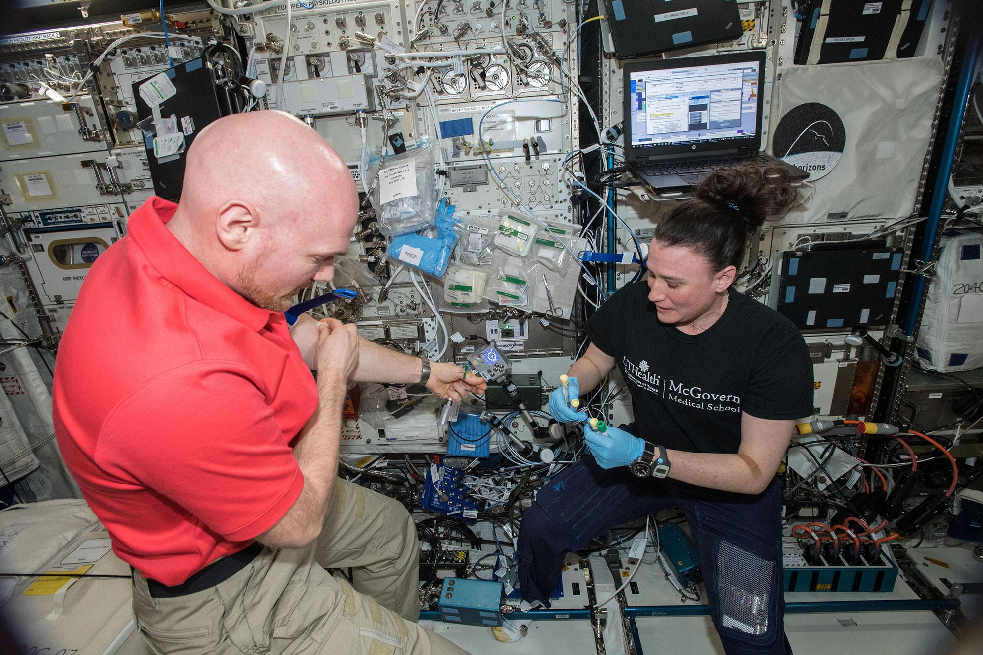 European Space Agency  astronaut Alexander Gerst and NASA astronaut Serena Auñón-Chancellor, during a functional immune blood sample draw at the Human Research Facility in the International Space Station's Columbus Module.