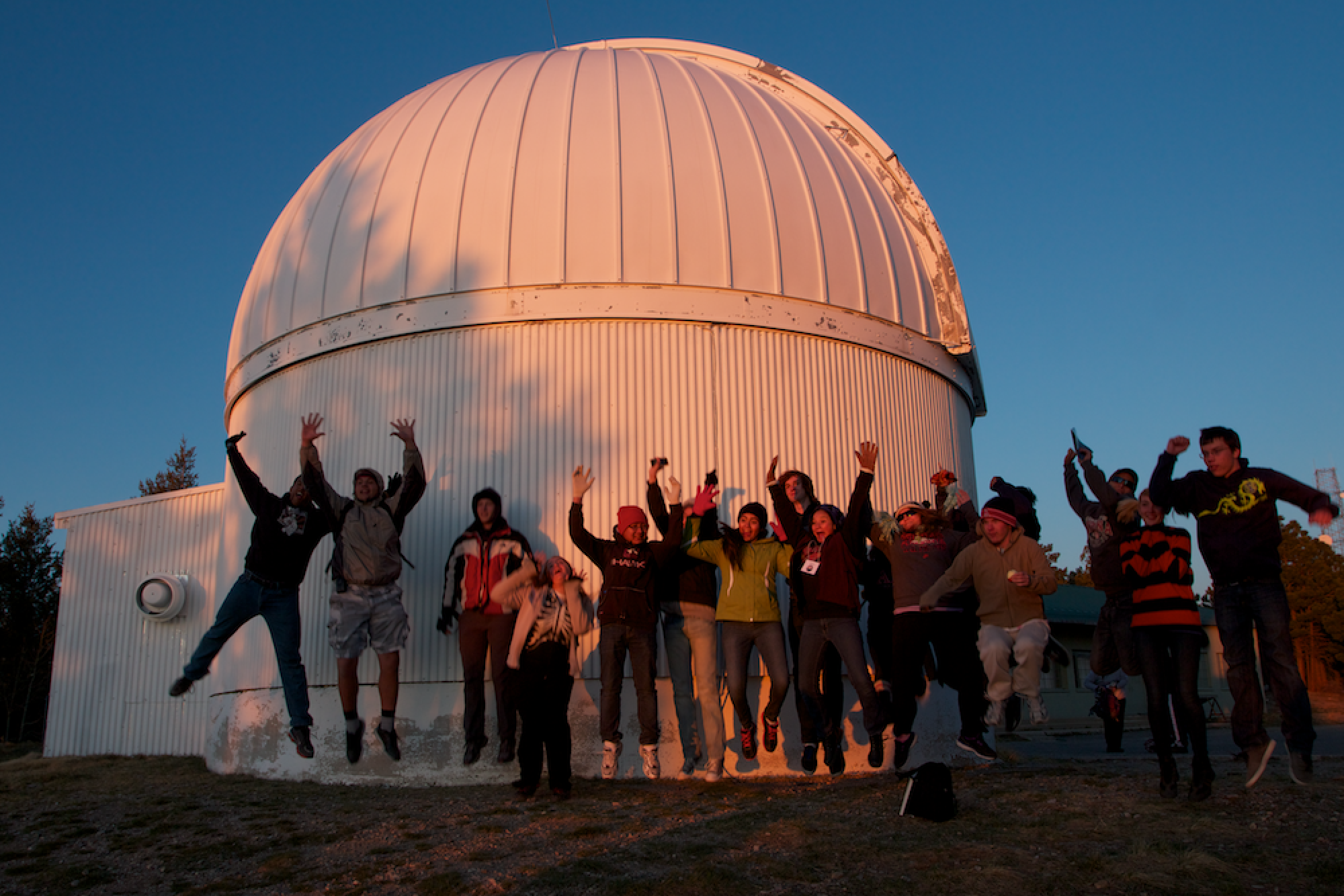 Students from Tucson schools bid farewell to the sun in front of one of the telescope domes at the UA's Mt. Lemmon SkyCenter.