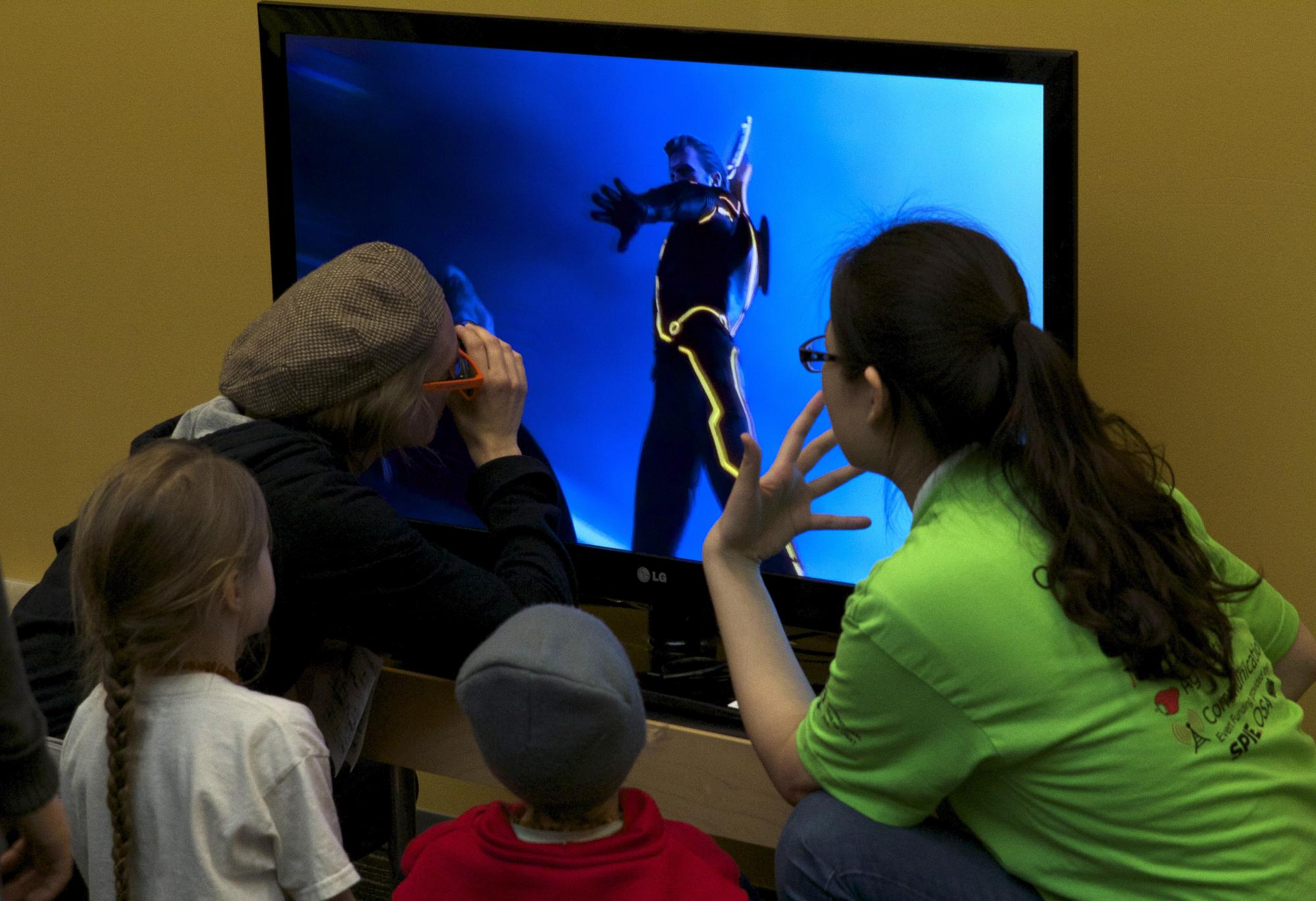 Visitors at the event explore 3-D television.