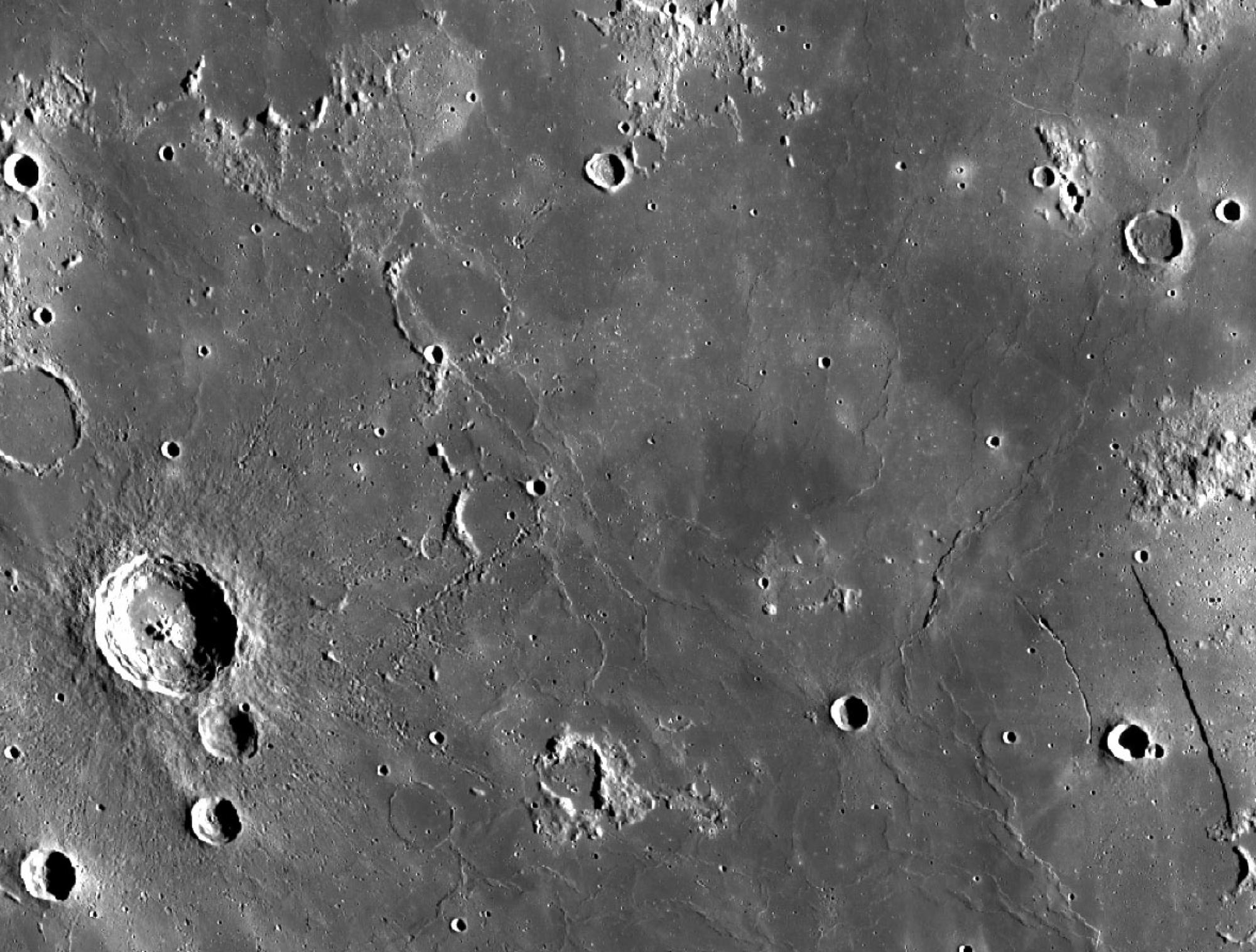 NASA's Lunar Reconnaissance Orbiter took this wide-angle photograph of Mare Nubium, a seemingly featureless expanse on the moon. The crater on the left is Bullialdus, which spans about 38 miles in diameter.