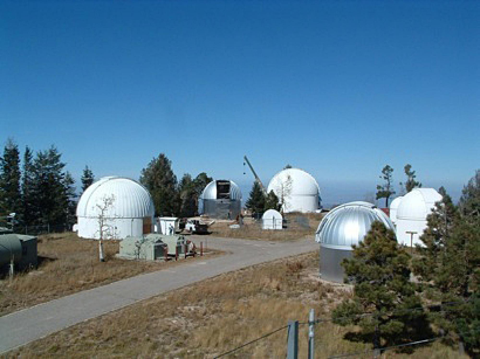 Overview of Steward Observatory's Mount Lemmon Observatory. The 24-inch SkyCenter telescope used for  public evening observations is at left. The silver-colored dome will house the Catalina Sky Survey's refurbished 40-inch telescope by summer. The white d