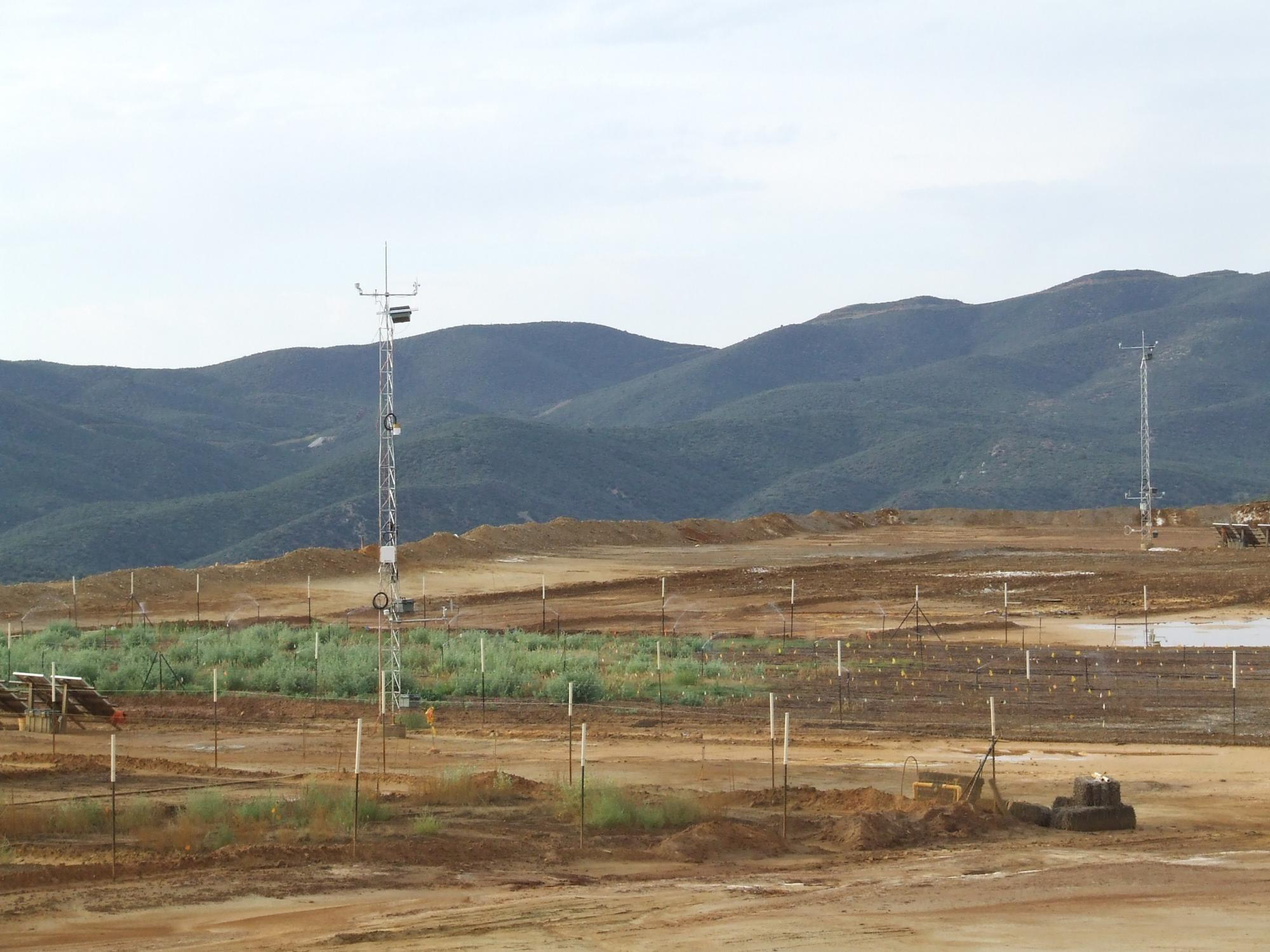A view of the Iron King mine tailings revegetation trial and the two dust flux towers set up to measure wind speed and direction, and dust movement. Desert plants were installed in the plots to determine which concentrations could stabilize the mine taili