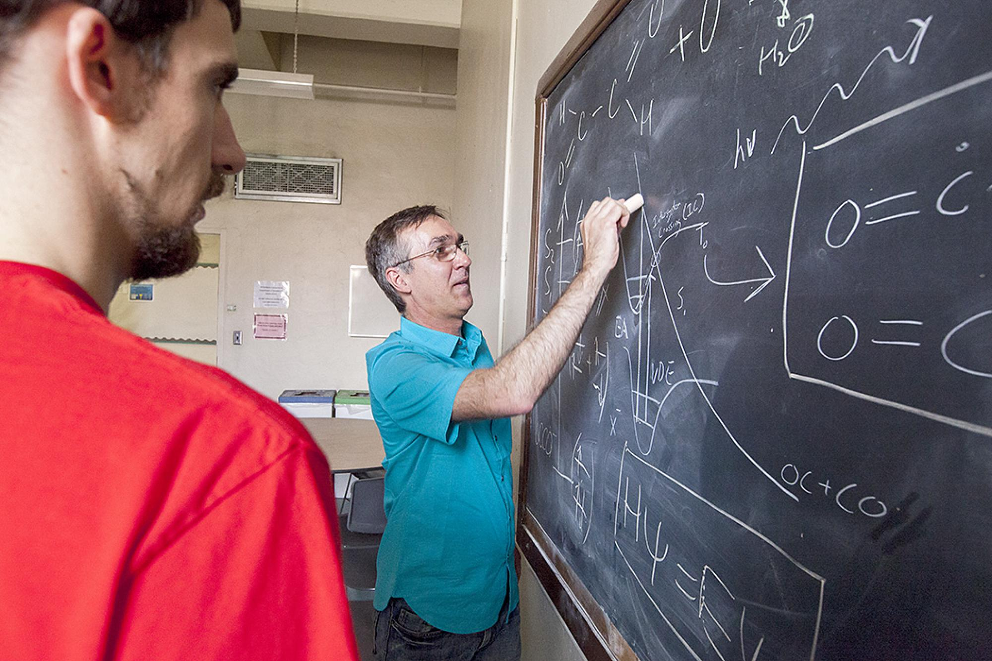 Sanov draws out the chemical reaction and formula of the long elusive ethylenedione  four-atom compound to team members Andrew Dixon, a doctoral student in chemistry, and Tian Xue, an undergraduate majoring in chemistry. The students were instrumental to