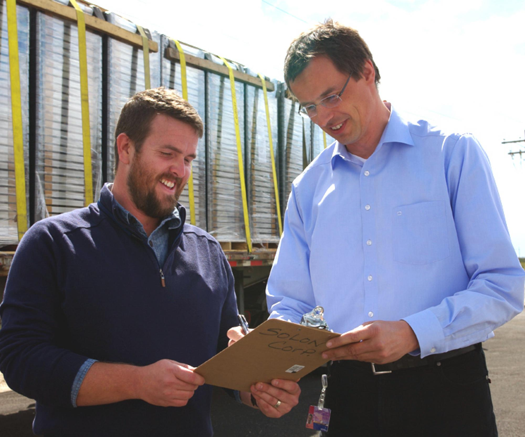 SOLON Corp. president and CEO Olaf Koester, right, signs paperwork for delivery of 470 photovoltaic modules for delivery to Biosphere 2. Nathan Allen of Biosphere 2 coordinated delivery of the panels, valued at $229,000.