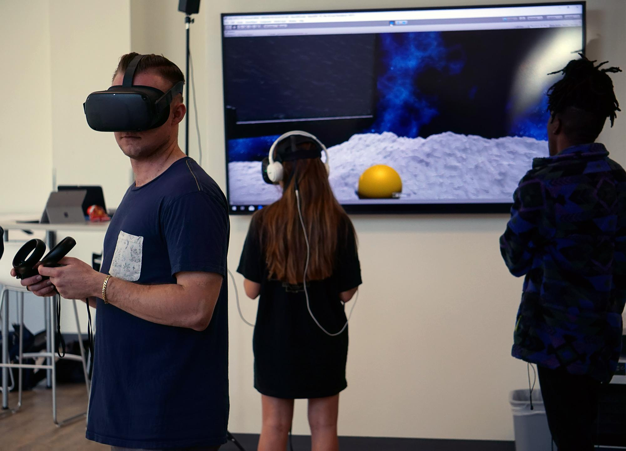 Tech Core coder Tim Lukau  stands by as two students simultaneously explore the Nano 2020 environment.