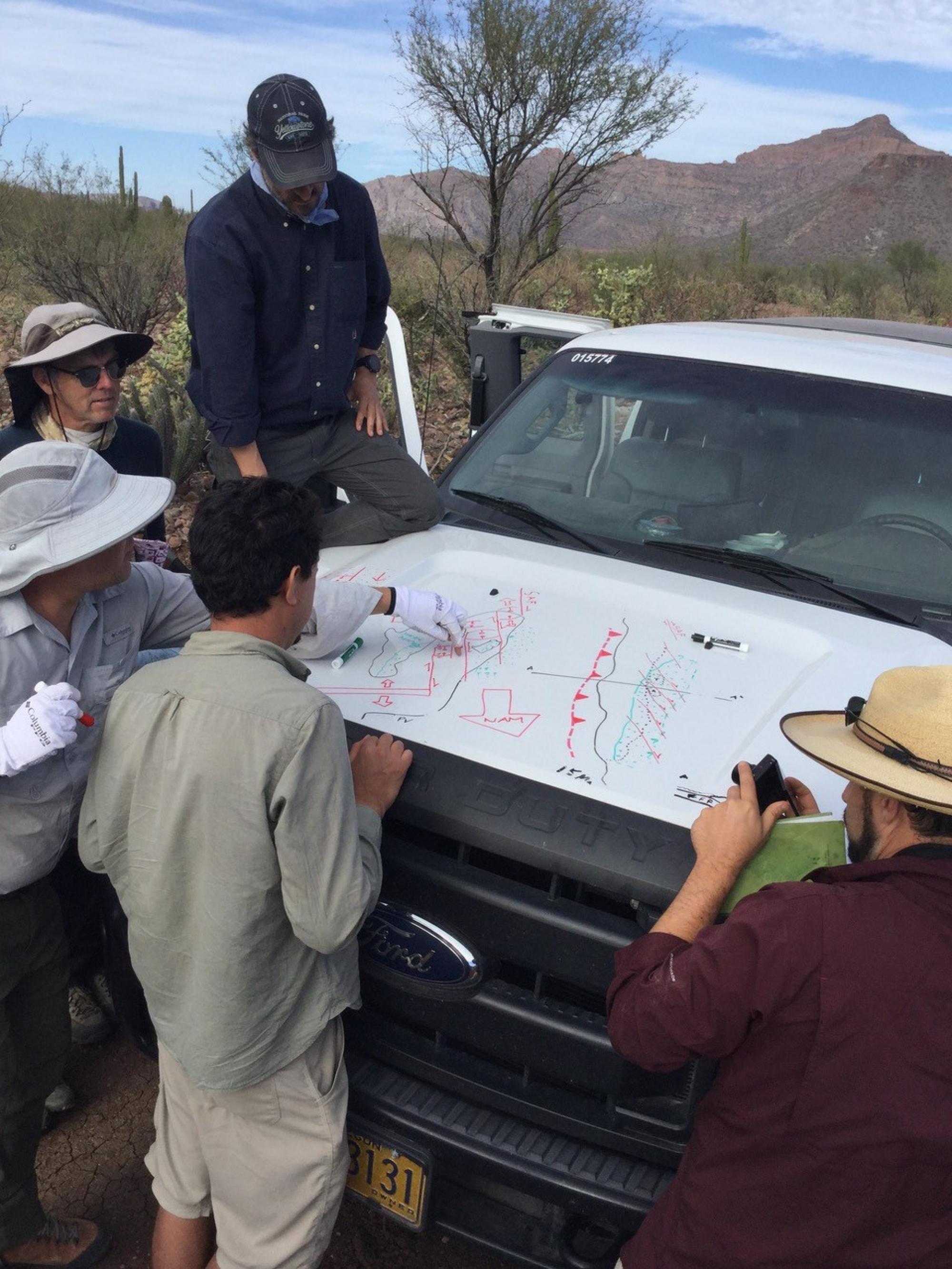 The Baja California Geogenomics team making geology doodles on the hood of their truck in the field near San Ignacio, Baja California Sur.