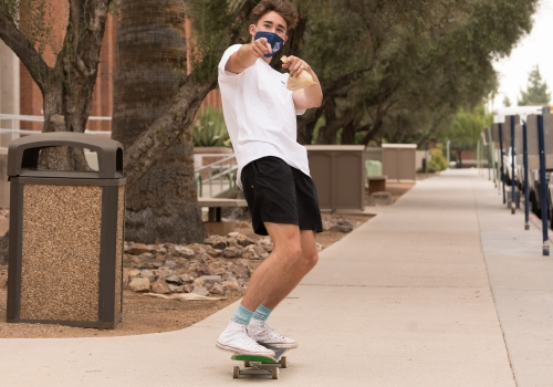 student with a face mask skateboarding on campus
