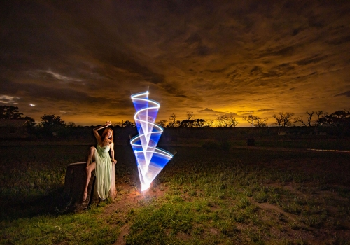 woman sitting in a field surrounded by a circle of light