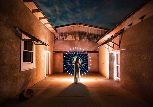 Woman standing in a barn surrounded by a circle of light