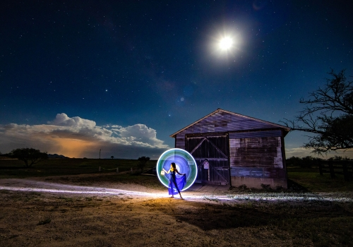 woman standing in front of a barn surrounded by a circle of light