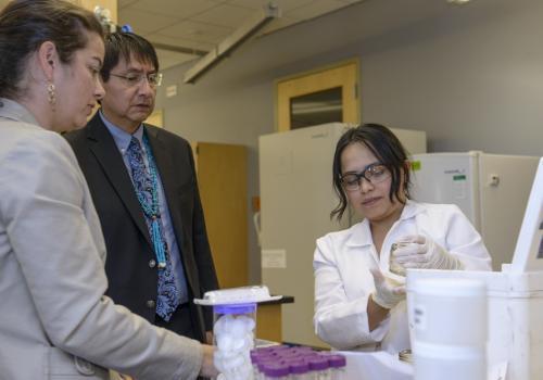 Paloma Beamer's doctoral student, Yoshira Ornealas Van Horne , inspects a water sample brought by Navajo Nation Vice President Jonathon Nez.