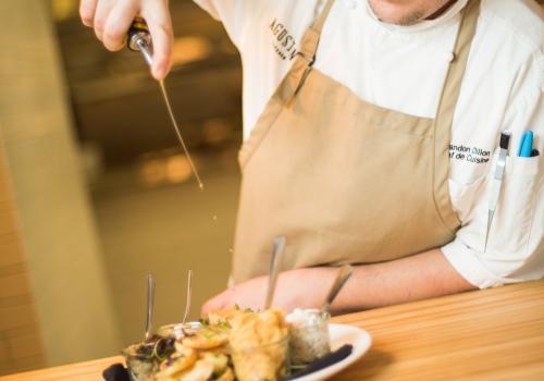 """Chef de Cuisine Brandon Dillon from the AgustÍn Kitchen prepares """"smears."""""""