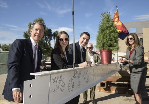 Five attendees stand next to a white steel beam decorated with signatures. From left: Gregg Goldman, UA senior vice president for business affairs and chief financial officer; Aundrea DeGravina and Vianney Careaga, student members of the Arizona Board of