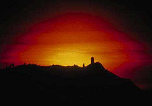 A distant shot of the setting sun backlights the Kitt Peak telescope domes in this photo, taken in 1982. At left is the distinctive triangular shadow of the National Solar Observatory's McMath-Pierce Solar Facility. At far right is the 4-meter Mayall