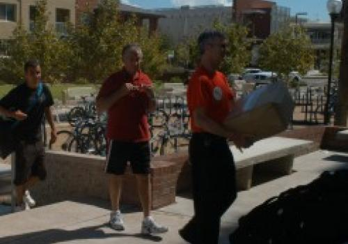 President Shelton helping new UA student move in to residence hall.