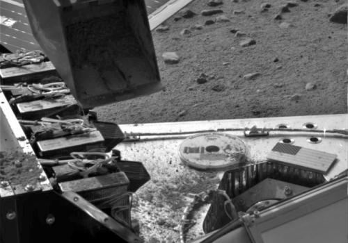 This image taken by the Surface Stereo Imager on NASA's Phoenix Mars Lander shows the lander's Robotic Arm scoop positioned over the Wet Chemistry Lab delivery funnel on Sol 29, the 29th Martian day after landing, or June 24 2008. The soil will be deliver