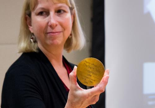 Karen Williams, dean of University Libraries, holds a bronze medallion. The medallions, inscribed with the names of the 1,177 sailors and Marines who lost their lives onboard the USS Arizona, will be part of the memorial.