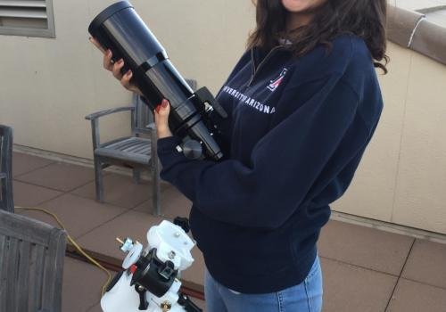 Adriana Mitchell holds one of the CATE telescopes during a practice run. During the total eclipse, 68 identical instruments will work in sync to photograph the sun's corona over an unprecedented time.