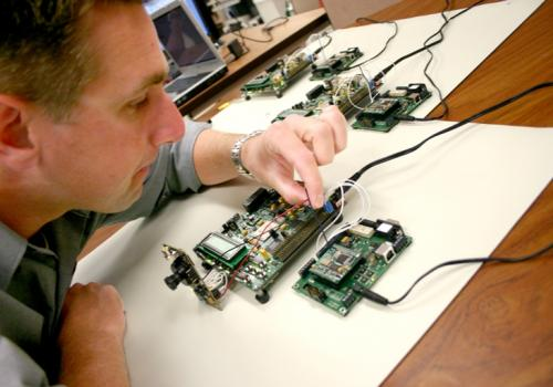 Kevin Carr, an undergraduate in electrical and computer engineering, adjusts one of the transmitter modules that is used to wirelessly link five units being tested in a self-healing computer system. The unit to the left of the transmitter is a Field Progr