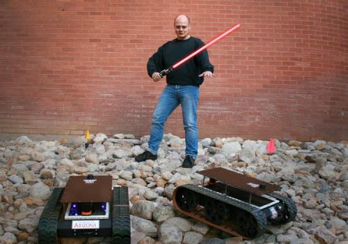 UA researcher Wolfgang Fink, with lightsaber, stands between two of the Mars rovers built in his laboratory.