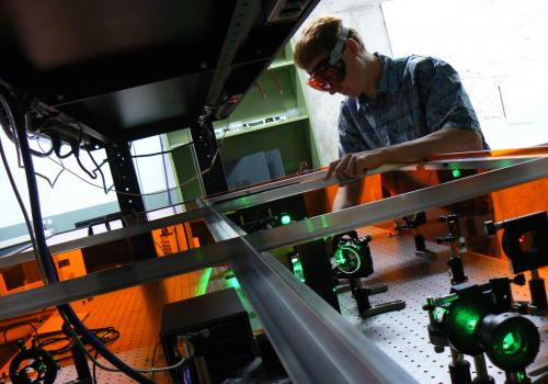 A researcher in the College of Optical Sciences prepares an experimental setup for testing data transmission using light.