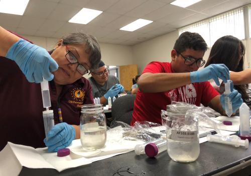 A Navajo Community Health representative and Diné Tribal College student work side by side filtering water samples taken along the San Juan River in Shiprock, Arizona.
