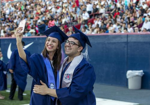 Amanda Ochs, an architecture graduate from Cave Creek, Arizona, and Stefano Saltalamacchia, a cultural understanding major from Ontario, California, pose for a selfie at Commencement.