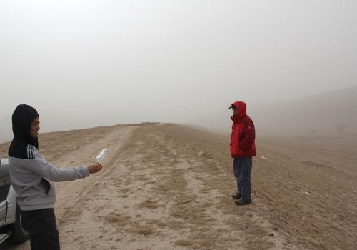 During a windstorm on China's Loess Plateau, geoscientist Fulong Cai uses a plastic bag as a wind sock to show that the wind blows parallel to the linear ridge he and Wang Zhao are standing on. Roads in this area run along the ridges.