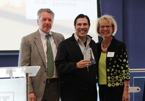 Remy Arteaga  accepts the award for the UA McGuire Center of Entrepreneurship, with David Allen and Kimberly Espy.