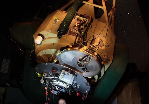 Robert McMillan observing with an experimental instrument unrelated to his asteroid work in 2007, in the dome of the Steward Observatory's 2.3-meter Bok Telescope on Kitt Peak.