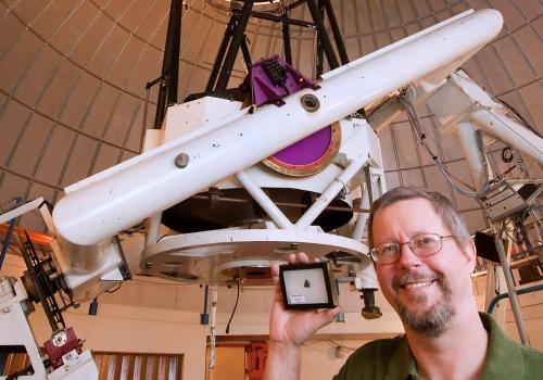 Richard Kowalski of the UA-operated Catalina Sky Survey holds a piece of 2008 TC3, the first-ever meteorite discovered while still cruising through space.