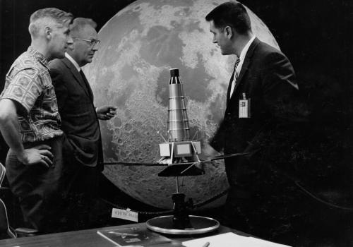Lunar researcher Ewen Whitaker, astronomer Gerard Kuiper, both from the UA Lunar and Planetary Lab, with Raymond Heacock from NASA's Jet Propulsion Lab, posing with a model of the Ranger spacecraft used for early moon missions. The same moon hemisphere m